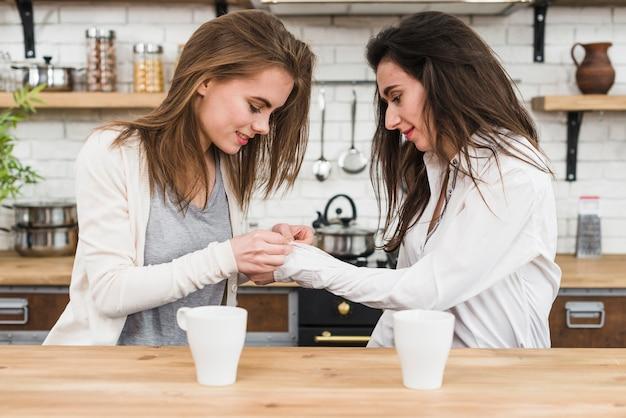 Die lesbische frau, die das hemd ihrer freundin knöpft, legt in der küche beiseite Kostenlose Fotos