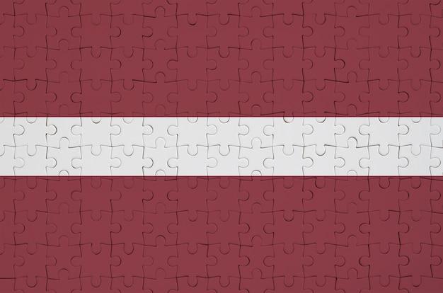 Die lettische flagge ist auf einem gefalteten puzzle abgebildet Premium Fotos
