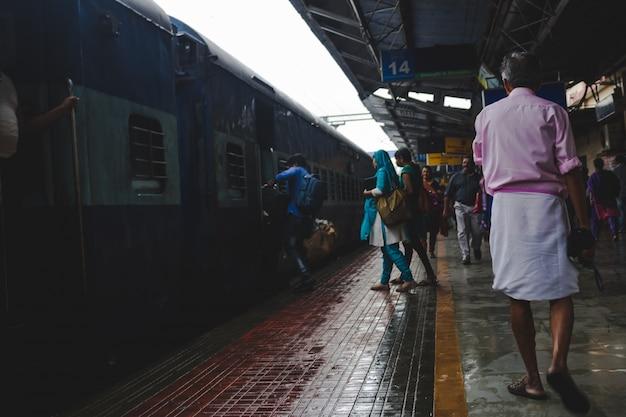 Die Leute eilen, um einen Zug als Mann in einem rosa Hemd zu gehen, geht vorbei Kostenlose Fotos