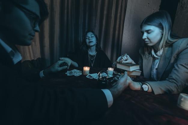 Die leute halten die hände der nacht am tisch mit kerzen Kostenlose Fotos