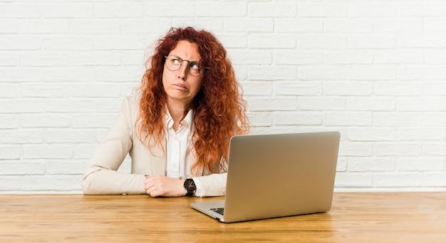 Die lockige frau der jungen rothaarigen, die mit ihrem laptop verwirrt arbeitet, fühlt sich zweifelhaft und unsicher. Premium Fotos