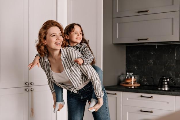 Die lockige mutter in jeans spielt mit ihrer tochter in der küche und lacht. Kostenlose Fotos