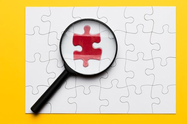 Die lupe, die auf rotes puzzlespielstück sich konzentriert, schloss an weißes stück an Kostenlose Fotos