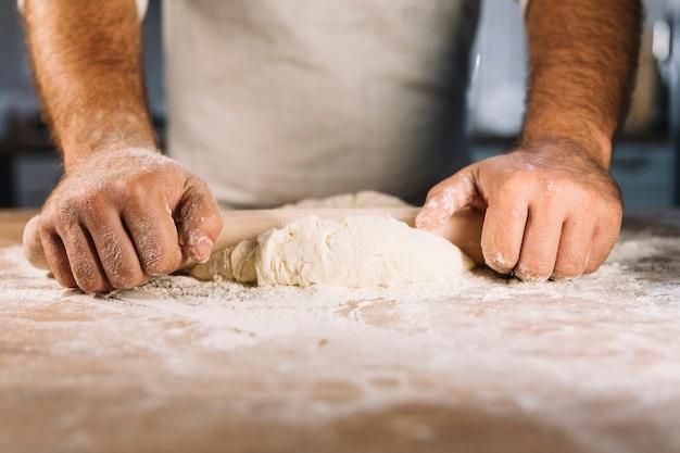 Die männliche bäckerhand, die teig mit nudelholz flach macht Kostenlose Fotos