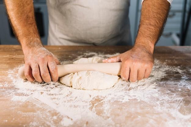 Die männliche hand des bäckers, die teig mit nudelholz auf holztisch flach macht Kostenlose Fotos