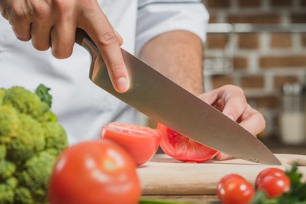 Die männliche hand des chefs, welche an die tomate mit scharfem messer an bord schneidet Kostenlose Fotos