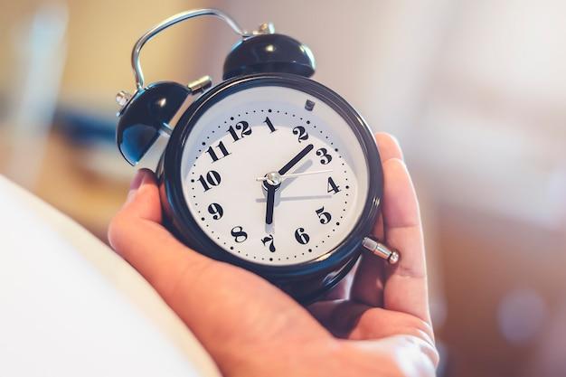 Die mannhand, die wecker für hält, wachen um 7.00 uhr morgens rechtzeitig mit lichteffekt in der warmen weinleseart des schlafzimmers auf Premium Fotos
