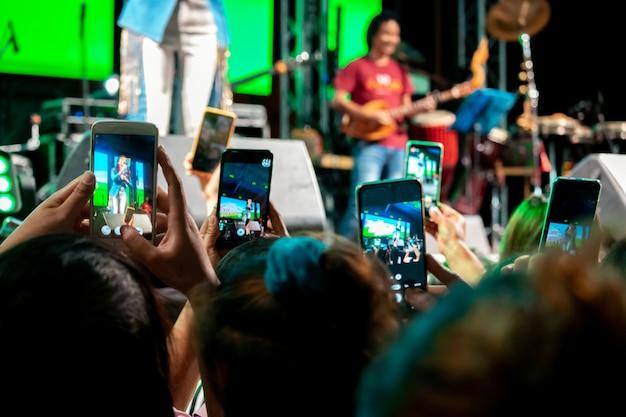 Die menschen nutzen mobiltelefone, um bei konzerten zu leben oder bilder zu machen, bei hellen lichtern in der nacht. Premium Fotos