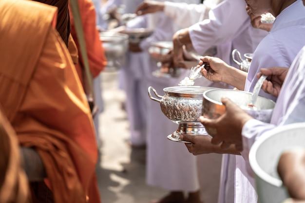Die mönche des buddhistischen sangha (geben einem buddhistischen mönch almosen) Premium Fotos