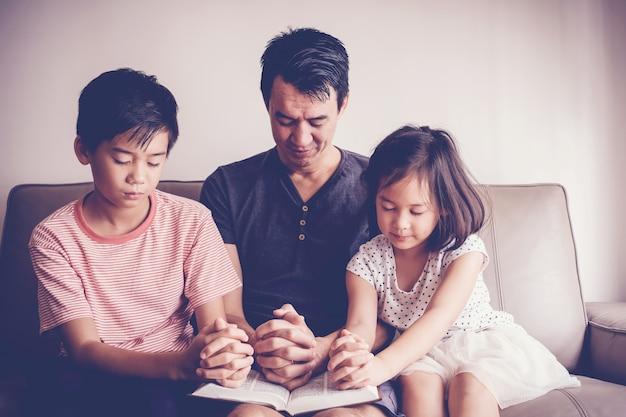 Die multikulturellen asiatischen kinder, die zu hause mit ihrem vater beten, familie beten Premium Fotos