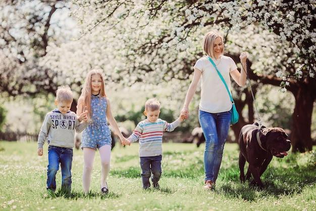 Die mutter, die kinder und der hund, die entlang park gehen Kostenlose Fotos