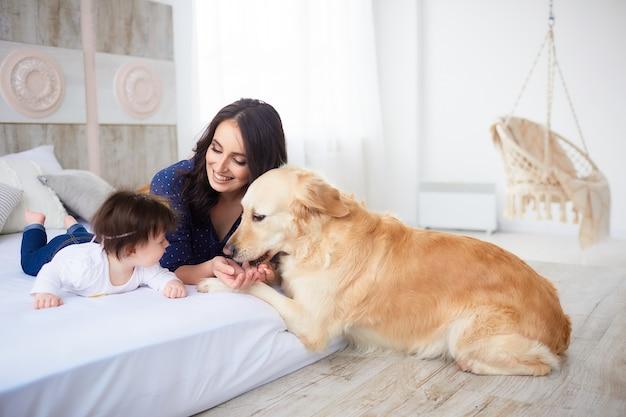 Die mutter mit der tochter liegt auf dem bett und der hund, der sie betrachtet Kostenlose Fotos
