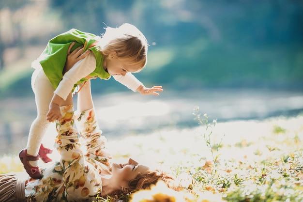 Die Mutter und die Tochter liegen auf dem Gras Kostenlose Fotos