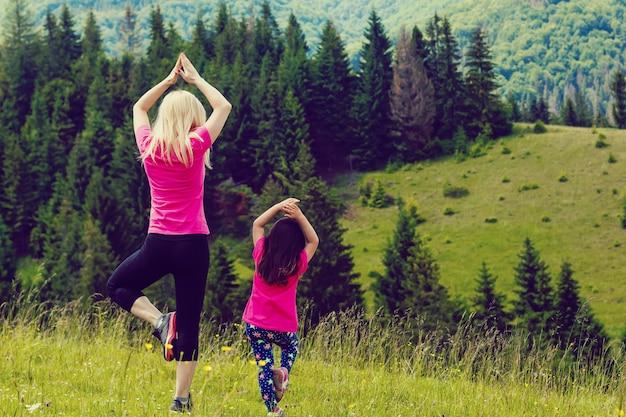 Die mutter und tochter, die yoga baum tun, werfen oben auf berg auf Premium Fotos