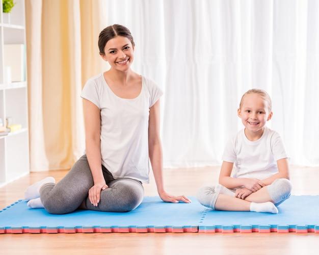 Die mutter und tochter, die yoga tun, trainieren auf wolldecke zu hause. Premium Fotos