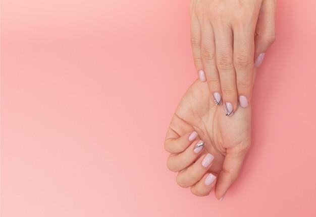 Die nägel der schönheit mit netter stilvoller maniküre auf rosa Premium Fotos