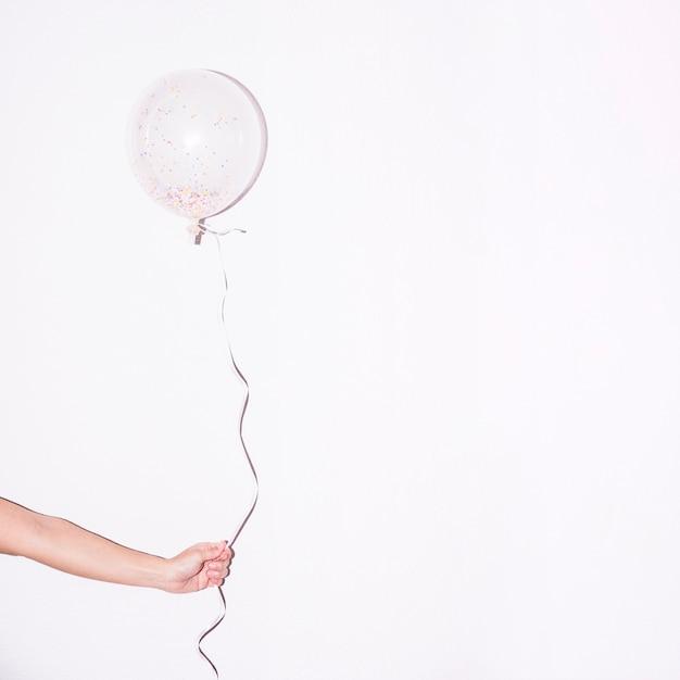 Die nahaufnahme der hand einzelnen weißen ballon mit buntem halten, besprühen innerhalb es gegen weißen hintergrund Kostenlose Fotos