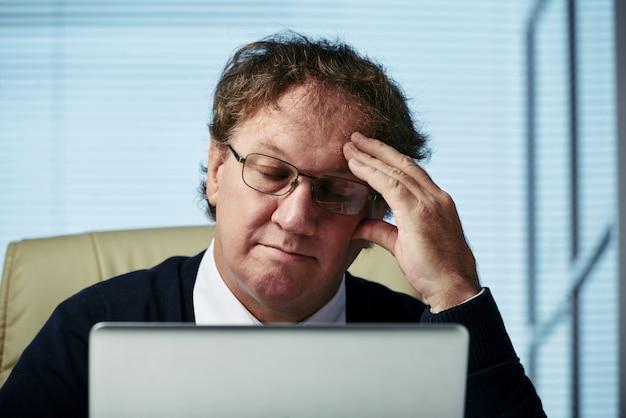Die nahaufnahme des mannes erwägend über geschäftsherausforderungsaugen schloss in seinem büro Kostenlose Fotos