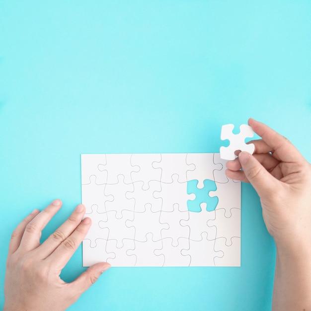Die nahaufnahme einer person, die das letzte stück hält, passt, um das puzzle zu vervollständigen Kostenlose Fotos