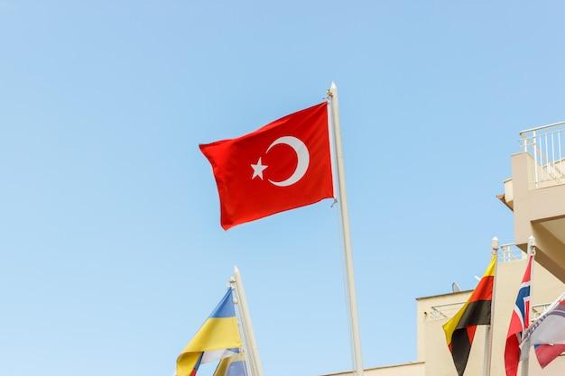 Die nationalflagge der türkei weht im wind gegen einen blauen himmel Premium Fotos