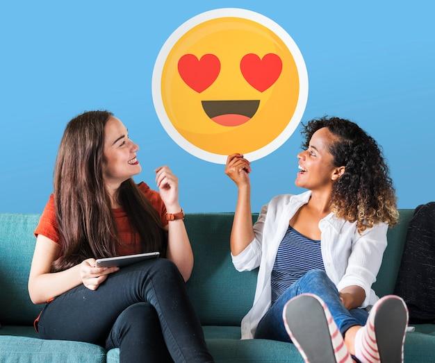 Die netten frauen, die ein herz halten, mustern emoticonikone Kostenlose Fotos