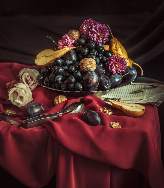 Die obstschale mit trauben und pflaumen gegen eine kastanienbraune tischdecke Kostenlose Fotos