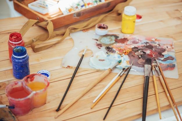 Die palette des künstlers. farbige ölfarben über eine palette auf einem tisch. Premium Fotos