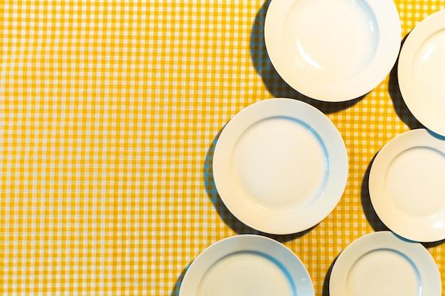 Die platte auf gelber karierter tischdecke Premium Fotos
