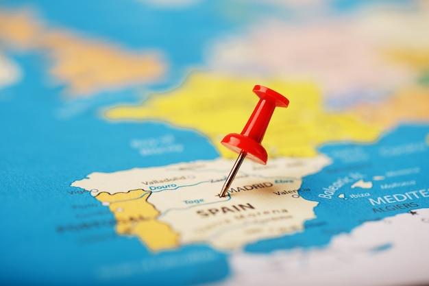 Die position des ziels auf der karte von spanien wird durch eine rote reißzwecke angezeigt. spanien markiert auf der karte mit einem roten knopf Premium Fotos