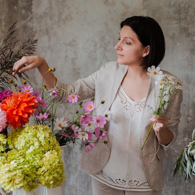 Die professionelle floristin bereitet die anordnung der wildblumen vor. Premium Fotos