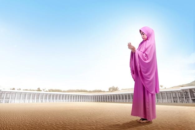Die recht asiatische frau im rosa schleier, der auf wüste steht, heben die hände an und schauen unten Premium Fotos