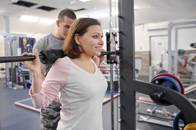 Die reife frau, die sport tut, trainiert mit persönlichem trainer an der turnhalle. Premium Fotos