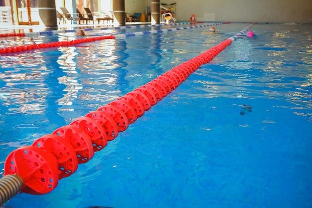 Die rot markierte bahn zur vorbereitung von schwimmwettkämpfen. sportbecken mit markierten bahnen. leerer pool ohne menschen mit ruhigem stehendem wasser. wassersport im innenpool, sportanlage. Premium Fotos