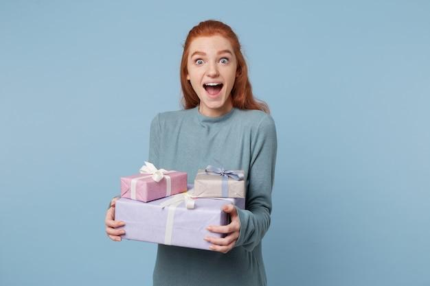 Die rothaarige frau, die kisten mit geschenken in den händen hält, steht mit weit geöffneten augen seitlich Kostenlose Fotos