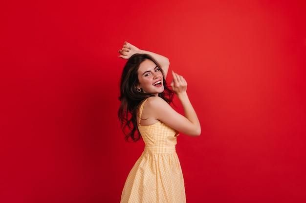 Die schelmische lockige dame tanzt auf der roten wand. brünette im gelben kleid lächelt aufrichtig und genießt fotoshooting. Kostenlose Fotos