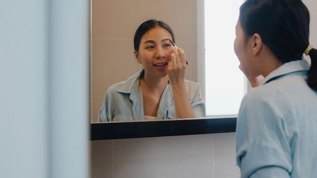 Die schöne asiatin, die augenbrauenstift verwendet, bilden im vorderen spiegel, die glückliche lateinische frau, die schönheitskosmetik verwendet, um sich zu verbessern, die zum im badezimmer zu hause arbeiten bereit ist. lifestyle-frauen entspannen zu hause. Kostenlose Fotos