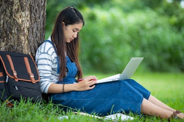Die schöne asiatische studentin, die bücher hält und auf park im sommer für lächelt und lernt und bildet, entspannen sich zeit Premium Fotos