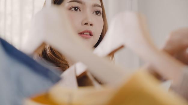 Die schöne attraktive junge asiatin, die zu hause ihre modeausstattung wählt, kleidet im wandschrank Kostenlose Fotos