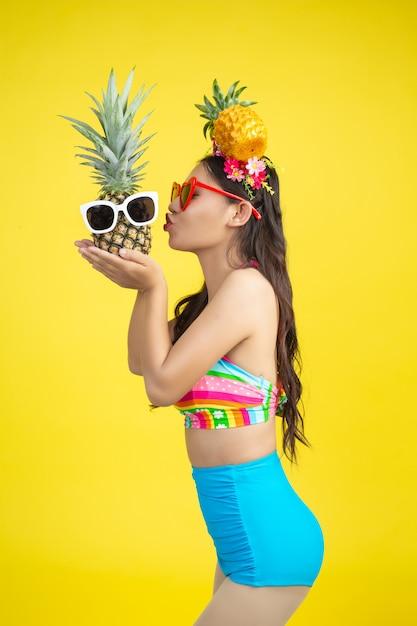 Die schöne frau in einem badeanzug, der eine ananas hält, wirft auf gelb auf Kostenlose Fotos