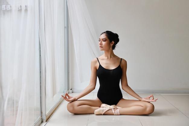 Die schöne gesunde asiatische frau im ballettkleid herein genießend meditiert mit yogahaltung zu hause mit entspannung Premium Fotos