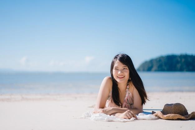 Die schöne junge asiatische frau, die auf dem glücklichen strand liegt, entspannen sich nahe meer. Kostenlose Fotos