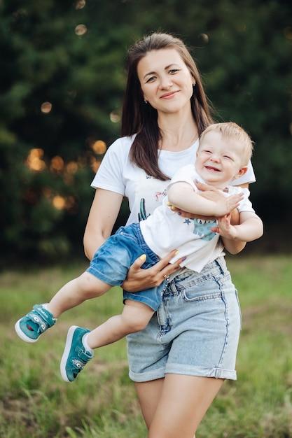 Die schöne junge mutter geht mit ihrem kleinen kaukasischen baby im park spazieren Premium Fotos