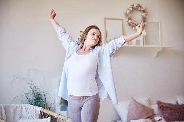 Die schöne junge schwangere frau, die morgen tut, trainiert zu hause. Premium Fotos