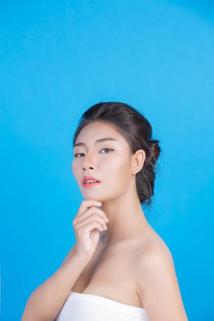 Die schönheit von frauen mit perfekten hautgesundheitsbildern berührt ihr gesicht und lächelt wie ein spa, um ihre haut blau zu verwöhnen Kostenlose Fotos