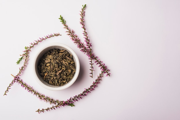 Die schüssel trockene blumenblätter, die mit lavendel umgeben werden, blüht auf weißem hintergrund Kostenlose Fotos