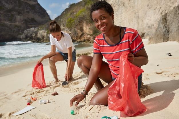 Die schwarze afroamerikanerin und ihr begleiter holen recycelbare plastikflaschen und anderen müll ab Kostenlose Fotos