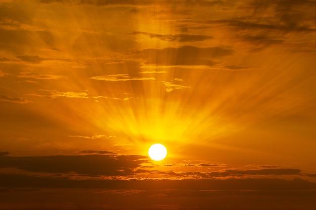Die sonne, die am himmel am sonnenaufgang- oder sonnenuntergangzeithintergrund scheint Premium Fotos