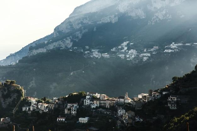 Die sonne scheint über das gebäude auf den bergen Kostenlose Fotos
