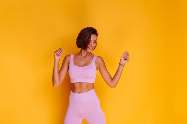 Die sportlerin steht auf einer gelben wand und zeigt ihre bauchmuskeln, ist mit den ergebnissen des fitnesstrainings und der ernährung zufrieden, hat einen glücklichen gesichtsausdruck, trägt ein sportoberteil und enge leggings Kostenlose Fotos