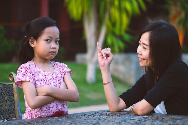 Die stirnrunzelnde tochter ist wütend und die mutter entschuldigt sich dafür, dass sie ihren kleinen finger gezeigt hat. Premium Fotos
